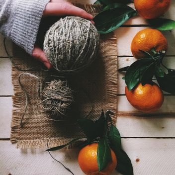 Skeins of wool and tangerines on white wooden background - бесплатный image #136259