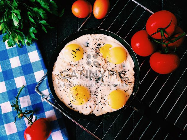Fried eggs, tomatoes and parsley on table - Free image #136509