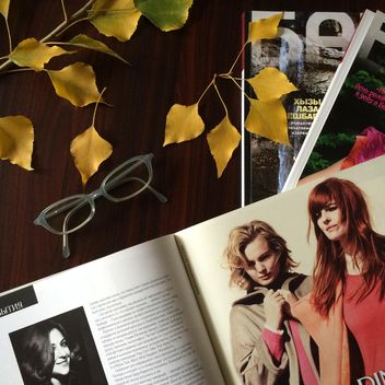 Magazines, glasses and autumn leaves on wooden table - image #182769 gratis