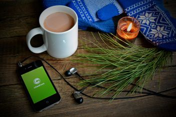 Candle, iPhone with earphones and Clashot logo and cup of coffee over wooden background - image gratuit #182789