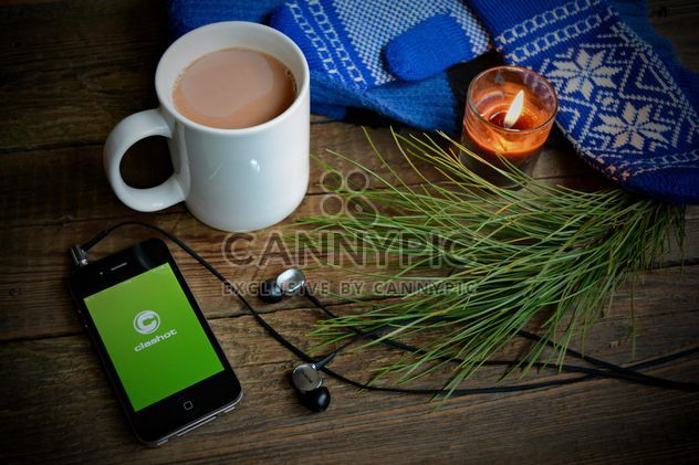 Candle, iphone with earphones and Clashot logo and cup of coffee over wooden background - Free image #182789