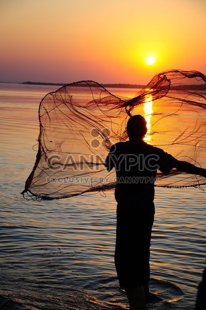 a fisherman throwing net through the sea #sunset - Free image #185769