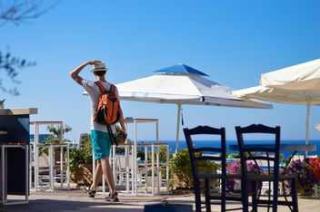 Man walking through outdoors cafe - image #186259 gratis