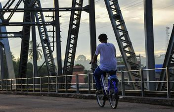 Man riding a bicycle across a bridge - image #186389 gratis