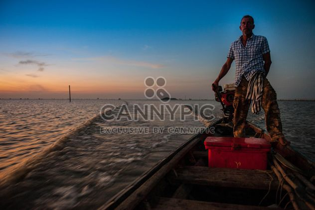 Fisherman in boat on sea at sunset - Free image #186589
