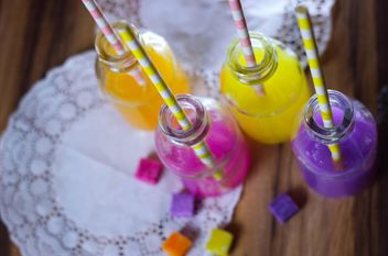 Bottles of colorful drinks - image #187619 gratis
