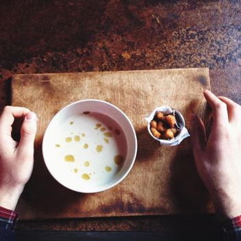 Human hands and bowl of soup on table - image #198499 gratis