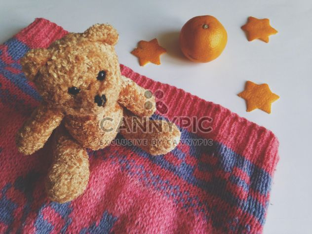 Children's sweater and a toy bear, tangerines on a white background - Free image #198789