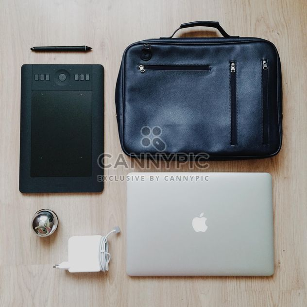 Tablet computer, e-book and black bag over wooden background - Free image #271729