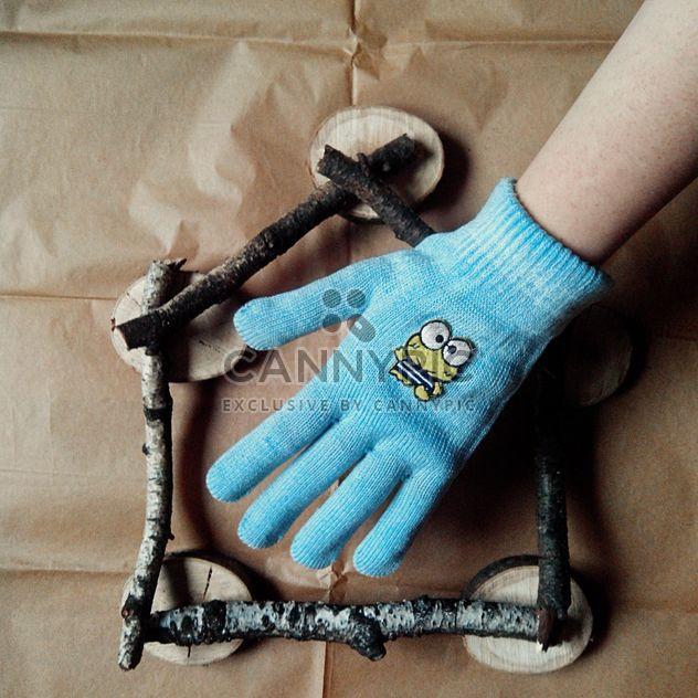 Mão na luva azul e casa feita de varas de madeira no fundo de papel bege - Free image #272239