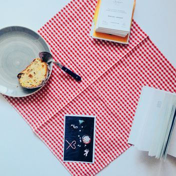 Cake on the plate, book and card on red checkered dishcloth - Free image #273869