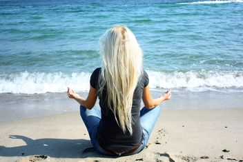 Blond girl meditating on a beach - image #273939 gratis