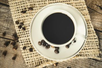A cup of coffee on a wooden board - image #302289 gratis