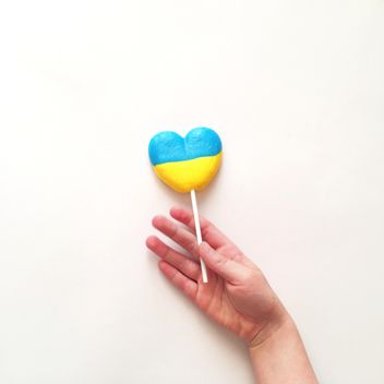 Child's hand and lollipop in colors of Ukrainian flag on white background - бесплатный image #329299