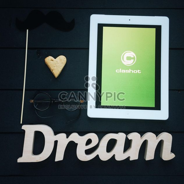 Tablet computer with Clashot logo and accessories on dark wooden background - Free image #329309