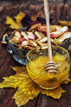 Honey in bowl and dried apples on wooden background - бесплатный image #330449