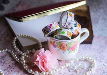 Scrapbook tape, jewelry, book near white cup - бесплатный image #341479