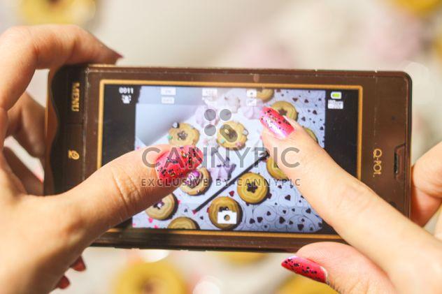 Smartphone decorado com enfeites de Natal nas mãos de mulher - Free image #342179