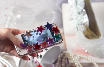 Smartphone decorated with tinsel in woman hands - бесплатный image #342189