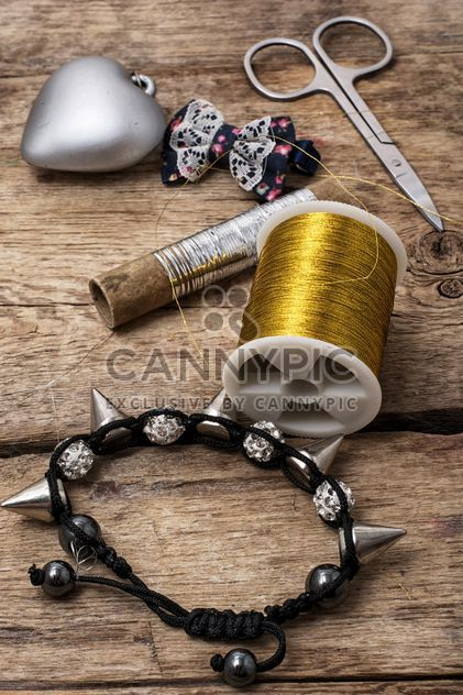 Bracelet and objects for sewing on wooden background - Free image #342599