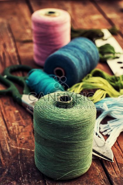 Scissors and colored sewing thread on wooden table - Free image #343559