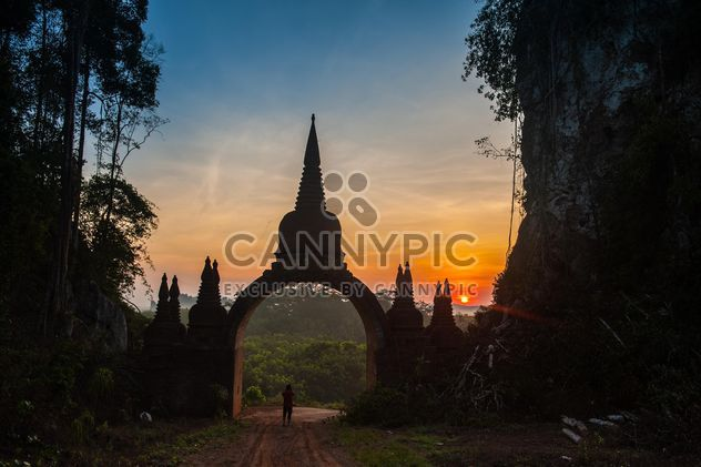 Man at gates to temple at sunset - Free image #344619