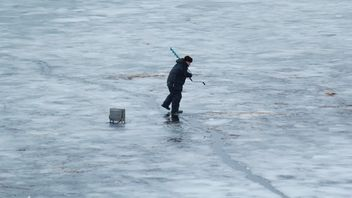 Fisherman during winter fishing on frozen river - бесплатный image #344629