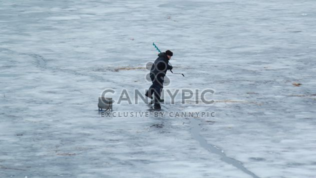 Fisherman during winter fishing on frozen river - Free image #344629