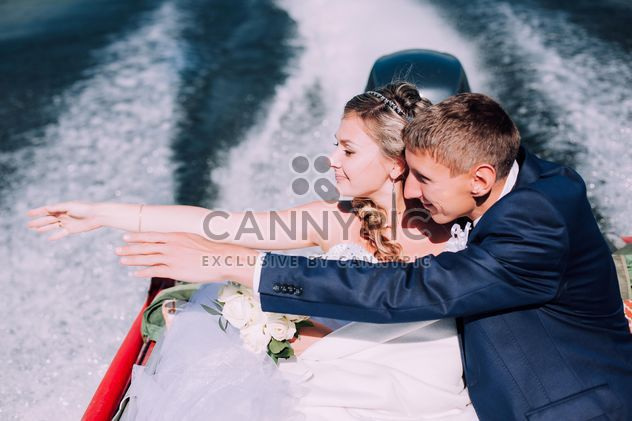 Happy wedding couple in boat on lake - Free image #345109