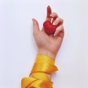 Red heart in female hand with yellow ribbon - бесплатный image #345879