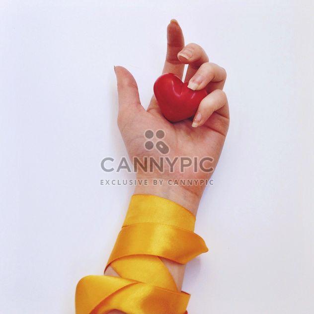 Corazón rojo en la mano femenina con cinta amarilla - image #345879 gratis