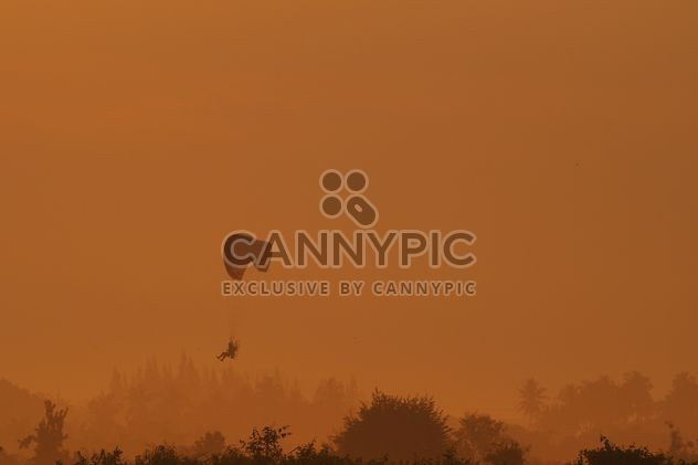 Flying paramotor in sky at sunset - бесплатный image #347019