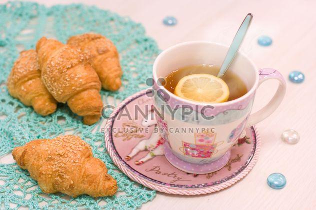 Taza de té caliente con limón y croissants - image #347909 gratis