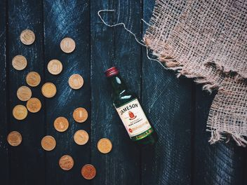 Small bottle of whiskey and coins on wooden background - бесплатный image #348639