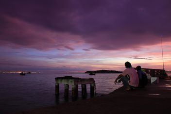 Fishermen sitting on waterfront at sunset - Free image #348949
