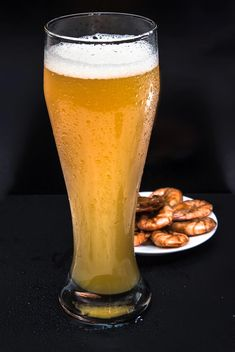 unfiltered cold foamy beer in a tall glass with a snack of fried shrimp - Free image #381019