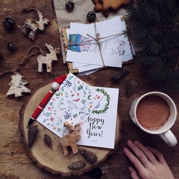 Toy deers, fir tree, New Year cards and cup of coffee over wooden background - бесплатный image #136279