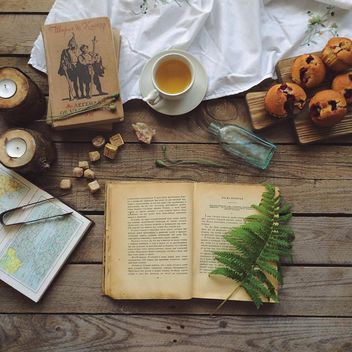 Open book, cup of tea and cupcakes - бесплатный image #136589