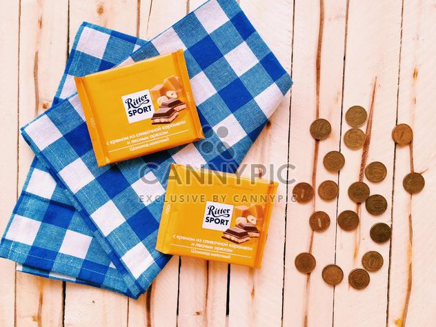 Two chocolate bars and coins on wooden background - image #183829 gratis