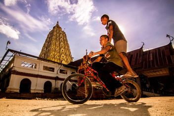 Two boys on a bicycle in Thai city - image #184189 gratis