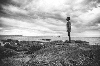Boy standing on rocks - image #185649 gratis