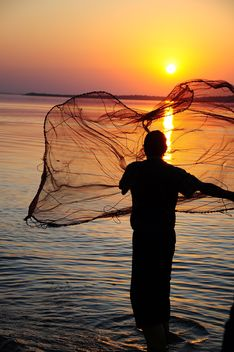 a fisherman throwing net through the sea #sunset - image #185769 gratis