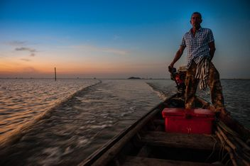 Fisherman in boat on sea at sunset - image #186589 gratis
