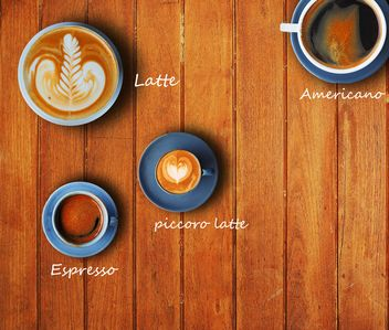 Cups of different coffee on wooden background - Free image #186959