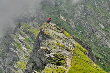 Alpinist hiking on mountain peak - бесплатный image #198159