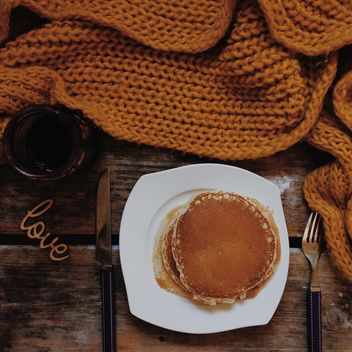 Pancakes in plate, jam and knitted scarf on wooden background - Free image #198379