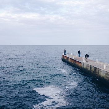 Fishermen on pier in sea - image #198549 gratis