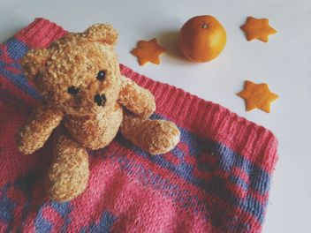 Children's sweater and a toy bear, tangerines on a white background - бесплатный image #198789
