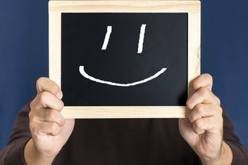 Man holding blackboard with happy smile in front of his face - бесплатный image #271599