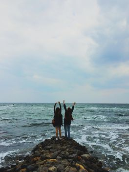 Two happy girls on the stones in the sea - image #271689 gratis